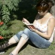 A student reads a book in the park sitting on grass — Stock Video #14038130