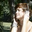 Young woman listening to music on headphones in the garden — Stock Video