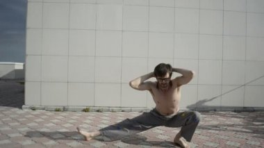 Man practices yoga on the roof. Squatting on one leg, hands behind his head. — Stock Video