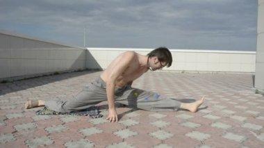 Um homem pratica ioga no telhado. fazer a abertura. — Vídeo stock
