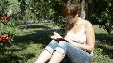 Young woman reading a book in the park sitting on grass — Stockvideo