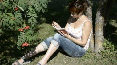 Een student leest een boek in het park zittend op het gras — Stockvideo