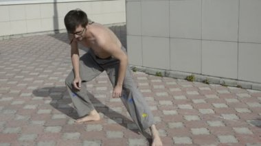 Man practices yoga on the roof. Warm up the legs with squats 2. — Stock Video