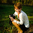 Young woman photographer in autumn park — Stock fotografie #14047364