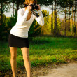 Foto Stock: Woman photographer in autumn park