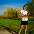 Business woman taking notes in a notebook while standing in autumn park — ストック写真