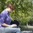 Young womuses laptop on park bench — Vídeo de stock #14041029