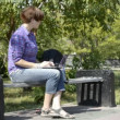 Girl uses a laptop on a park bench — Stock Video