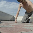 Stock Video: Mpractices yogon roof. To do push-up on with their fists 4.