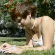 Young woman lying on the grass in the park and chatting — Stock Video