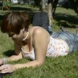 Young woman lying on grass with laptop — Stock Video