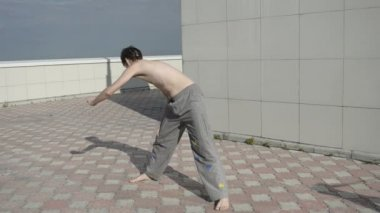 Man practices yoga on the roof. Rotations with flapping hands. — Stock Video