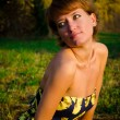 Young woman sitting on the grass in the autumn park — Stock fotografie #14076670