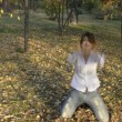 A young woman throws yellow leaves in autumn park — Stock Video