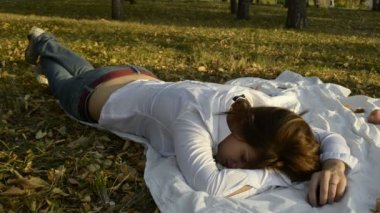 Young woman sleeping on a bedspread in the park and the autumn leaf fall — Stock Video