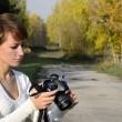 Young woman photographer in autumn park — ストックビデオ