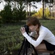 Stok video: Young woman photographer in autumn park