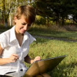 Businesswoman uses a laptop in autumn park sitting on the grass — Stock Video #18108597