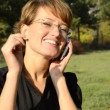 Young woman talking on a cell phone in park — Vídeo Stock