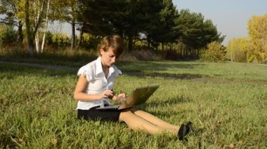 Businesswoman uses a laptop in autumn park sitting on the grass