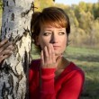 Young woman standing in autumn park under the birch — Stock Video