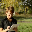 Young woman with a Tablet PC in the autumn park — Stock Video