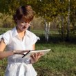 Young woman with a Tablet PC in the autumn park — Stock Video #18112967