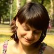 Young woman sitting on the grass in the park — Stock Video