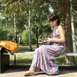 Young pregnant woman in the park gets a credit card — Stock Video #20796709