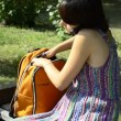 A young pregnant woman talking on the phone and digging in the backpack — Stock Video