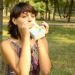 Young pregnant woman drinking juice in the park — Видео