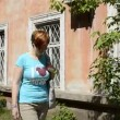 Young woman walks past an old brick house — Stock Video