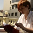 Young woman sitting at a table in a cafe, reading a book and drinking coffee — Stock Video