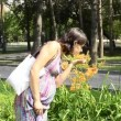 Young pregnant woman comes to flower bed — Stock Video #20797049