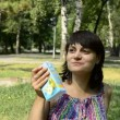 Young pregnant woman drinking juice sitting on the grass — Видео