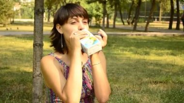 Young pregnant woman drinking juice in the park