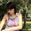 A young pregnant woman on the phone in the park — Stock Video