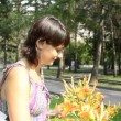 Young pregnant woman sniffing flowers — Stock Video