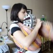 Young mother puts baby in a sling — Video