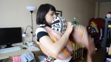 Young mother puts baby in a sling — Stock Video