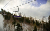 Lifting on the chair lift at ski resort — Stock Photo