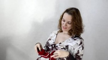 Young pregnant woman playing with baby booties sitting — Stock Video