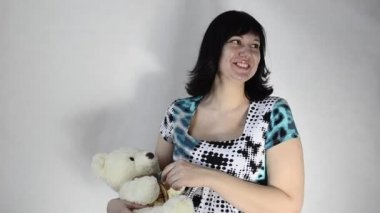 Young pregnant woman is playing with a toy bear and a baby pacifier — Stock Video