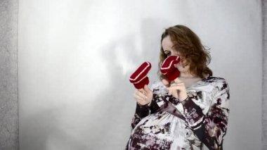 Mladá těhotná žena s baby botičky sedí na židli — Stock video