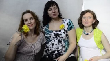 Three pregnant woman with yellow flowers in the studio — Stock Video
