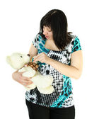 Young pregnant woman is playing with a toy bear and a baby pacifier — Стоковое фото