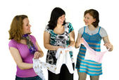Three pregnant women are looking clothes for babies — Stock Photo