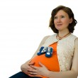 Pregnant adult woman playing with baby shoes sitting on a chair — Stock Photo