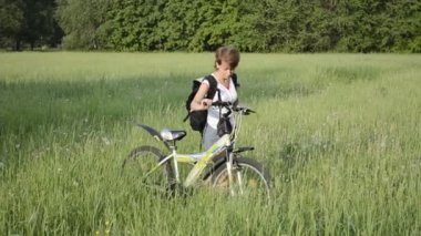 Woman with bicycle in summer field — Stock Video
