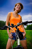 Young woman on a bicycle to the summer field — Stock Photo